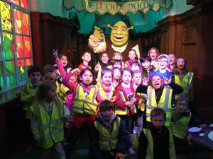 Children posing in front of a Shrek Statue
