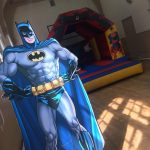 Batman poster in front of a Marvel Themed Bouncy castle