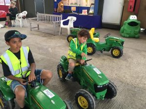 Kids sitting on two toy John Deere tractors
