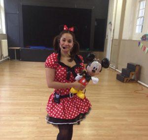 Minney mouse holding Mickey balloon
